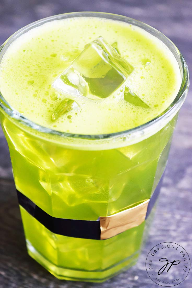 A glass wrapped with a leprechaun belt sits filled with this Green Lemonade Recipe.