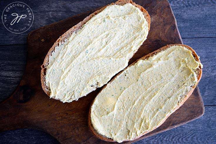 Spread the butter over both halves of the loaf of bread.