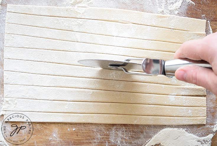 Cut the pasta dough into noodle-size strips.