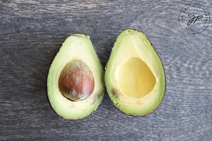 Cut avocado halves sit on a table. One side still has the seed in it.