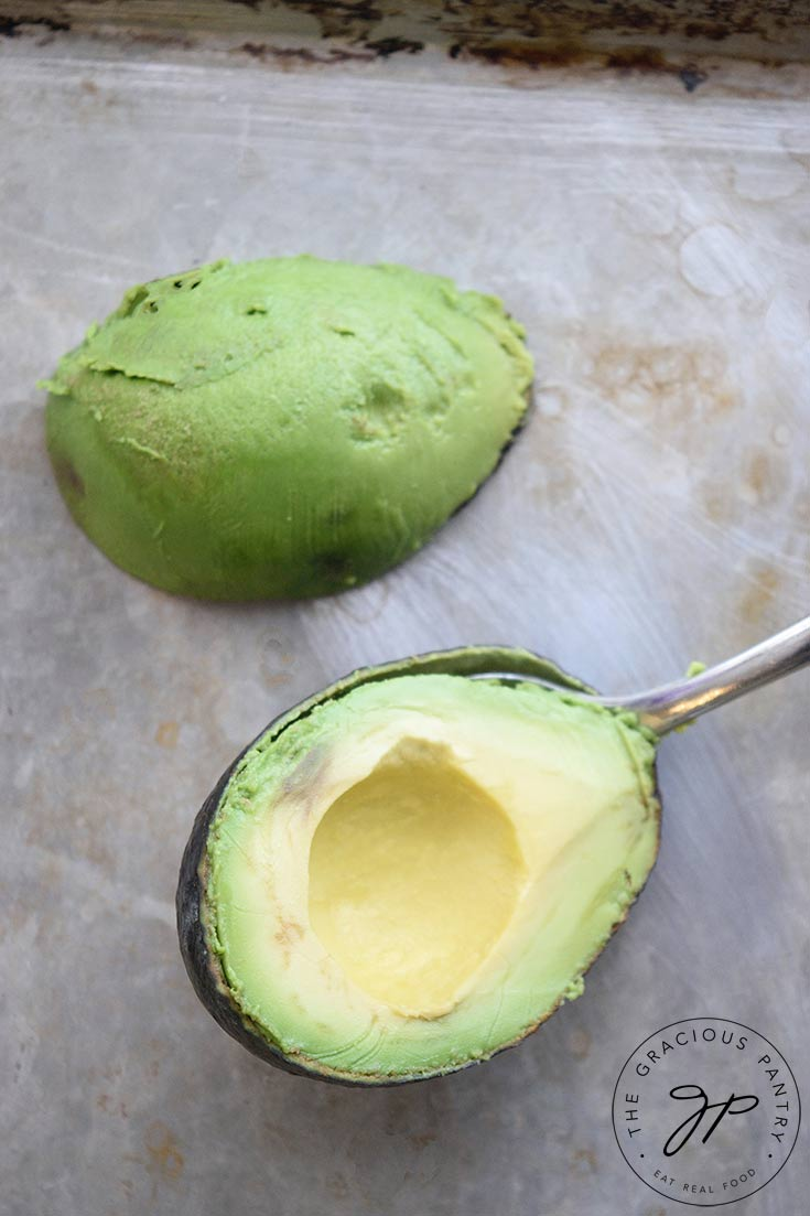 An avocado half with the skin removed, sits on a pan, ready to freeze. A spoon sits between the skin and flesh of the other half.