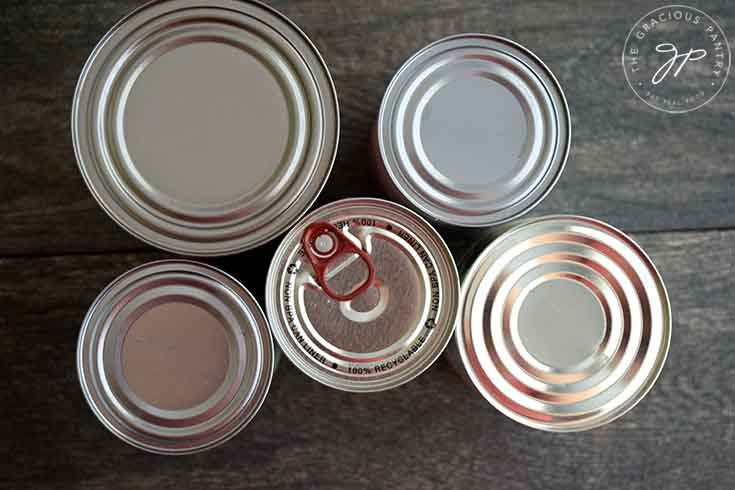 An overhead view of the tops of five cans in this collection of recipes for a can of whatever is in your cupboard or pantry.