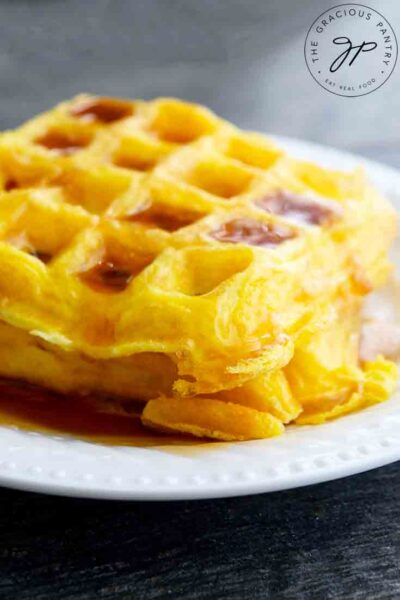 Bright, golden yellow egg waffles sit on a table, ready to serve and eat.