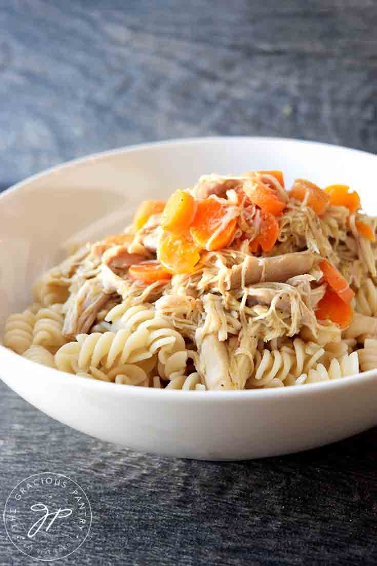 A bowl of Maple Chicken with carrot slices sitting on top.