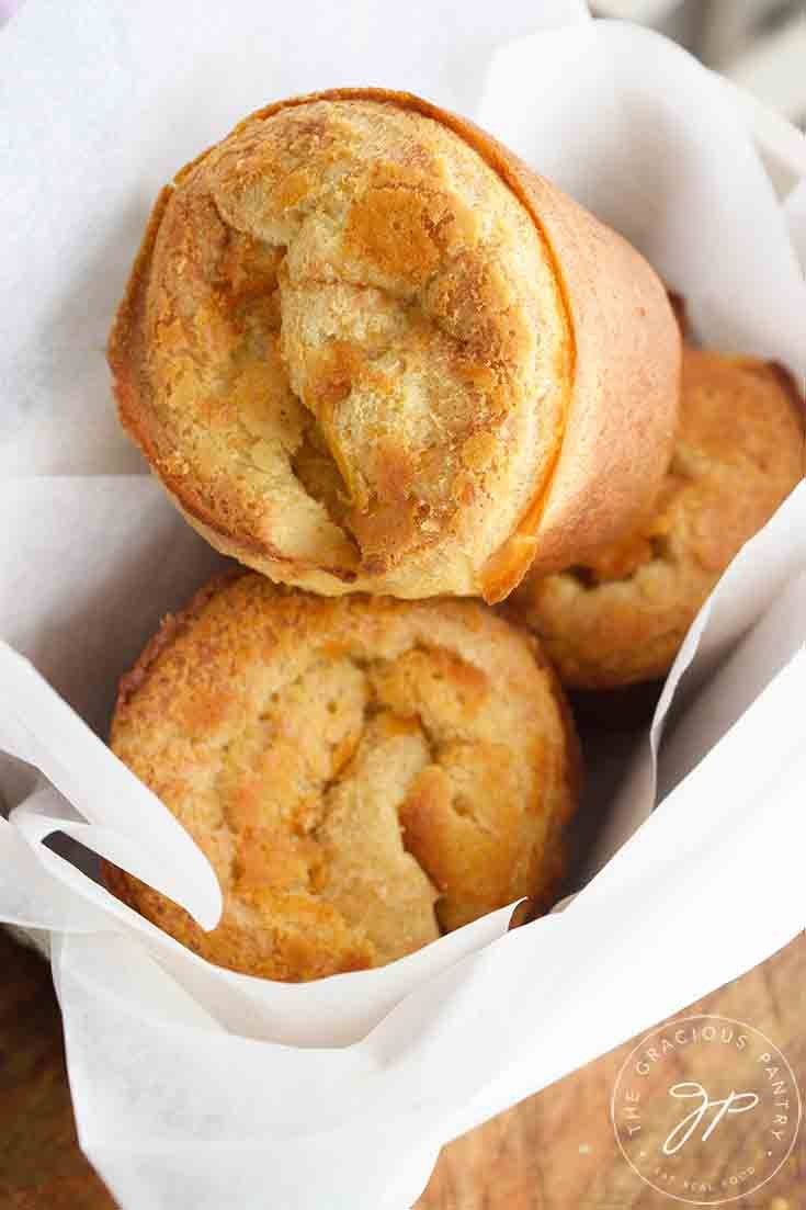 Three warm popovers in a small bread basket, ready to eat.