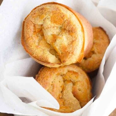 An overhead view of this popover recipe shows three popovers in a parchment lined bread basket.