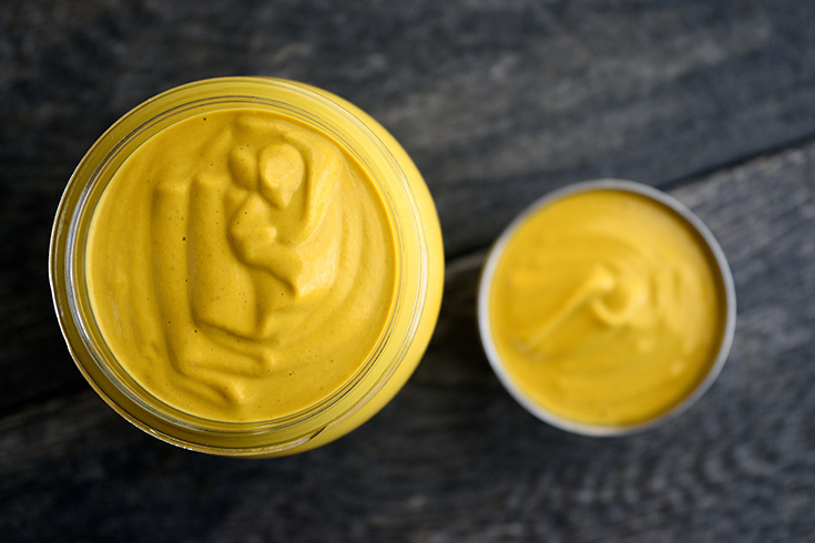 An overhead view looking down into an open jar and condiment container sitting next to each other, filled with this Vegan Cheese Sauce.