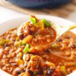A wooden spoon scoops out a big serving of this Beef Chili Recipe into a bowl.