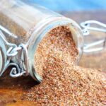 A spice jar filled with this Chili Spice Recipe sits tipped over with the spices spilling out onto a wood surface.