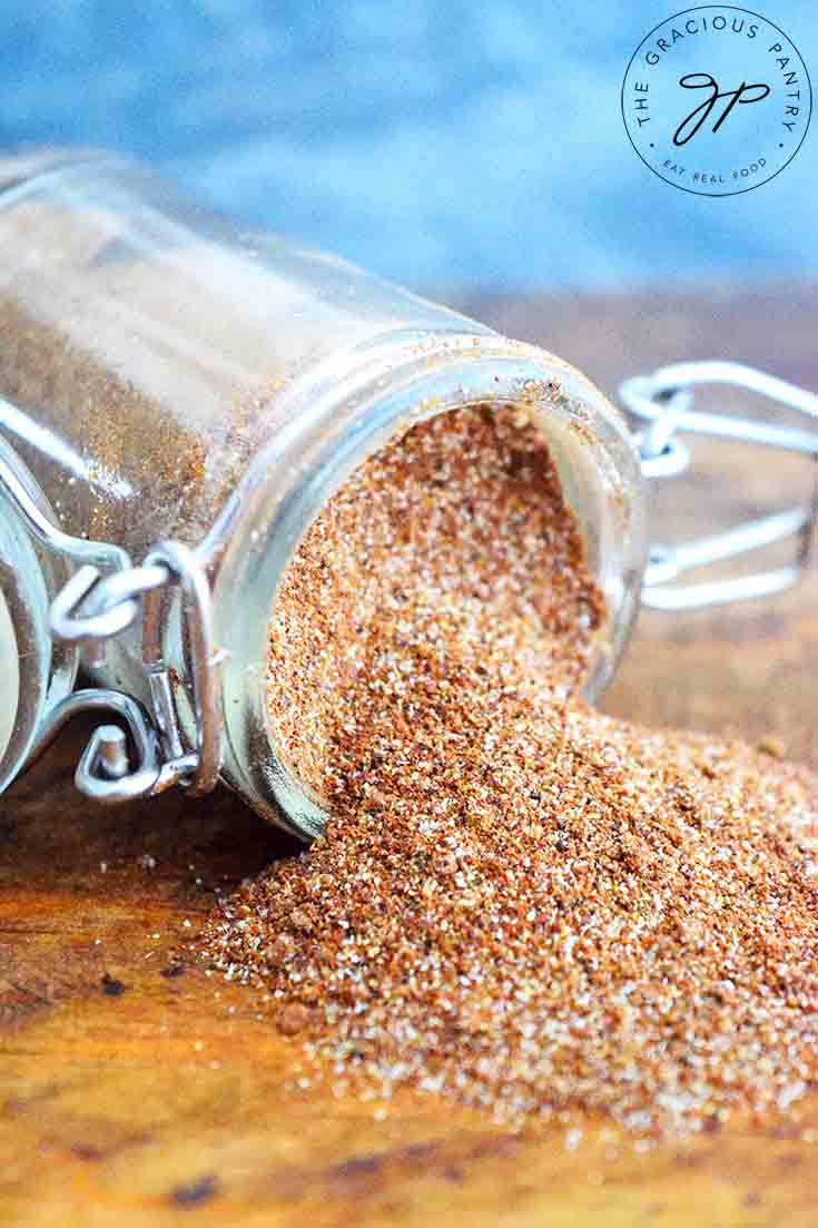 A spice jar filled with this Chili Seasoning Recipe sits tipped over with the spices spilling out onto a wood surface.