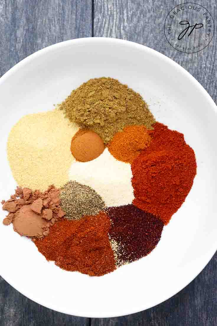 All the spices for this Chili Spice Recipe sit in a white bowl, waiting to be blended together. You can see each individual spice.