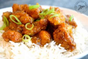 A horizontal shot of a bowl filled with Easy Orange Chicken.