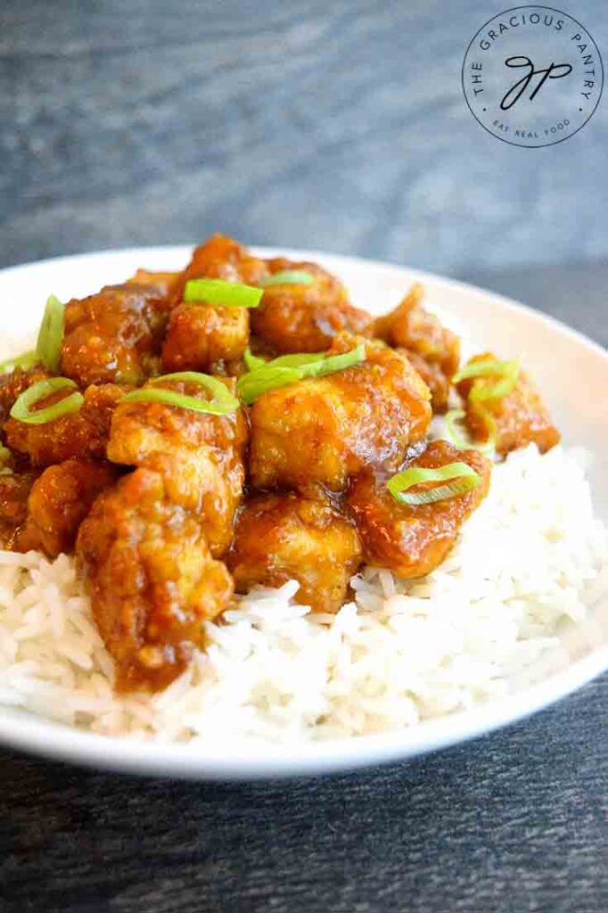 A front view of this bowl of Easy Orange Chicken topped with sliced green onions for garnish.