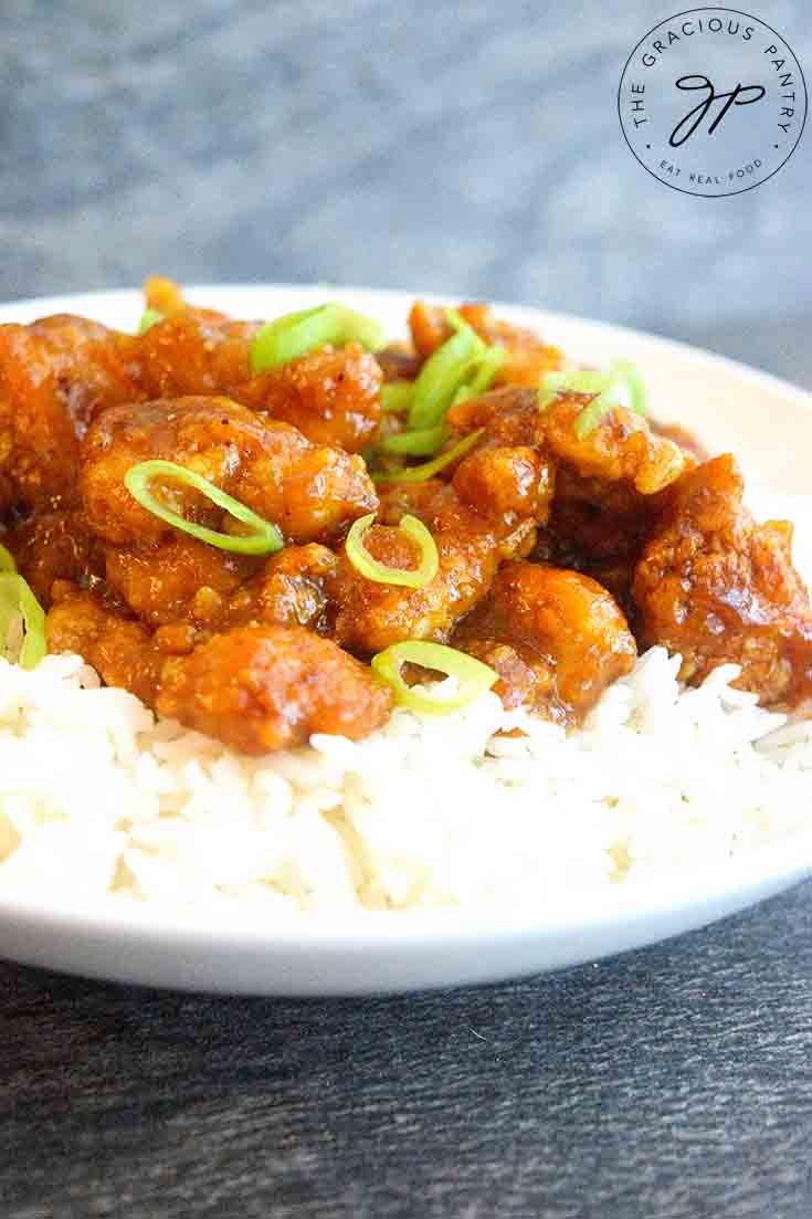 This Easy Orange Chicken sits on a bed of rice, served in a white bowl and topped with sliced, green onions.