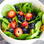 A side view of this delicious spinach salad recipe shows blueberries, sliced strawberries and walnuts layered in between the fresh spinach leaves.