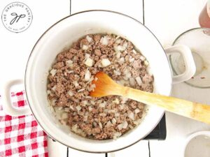 Browned beef in a pot with chopped onions added.