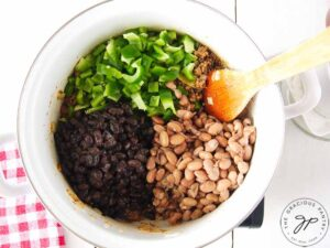 A pot with beans and green bell peppers.