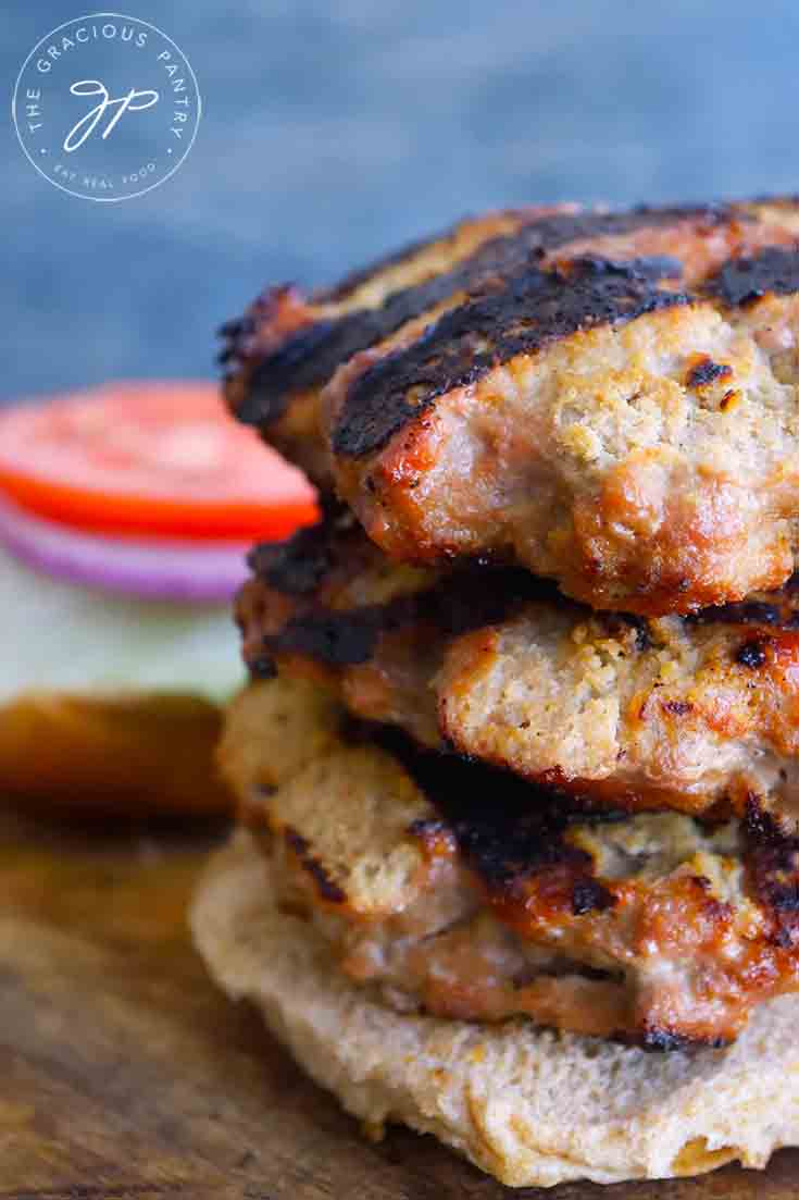 An up close shot of the three Grilled Turkey Burgers stacked high on half a burger bun.