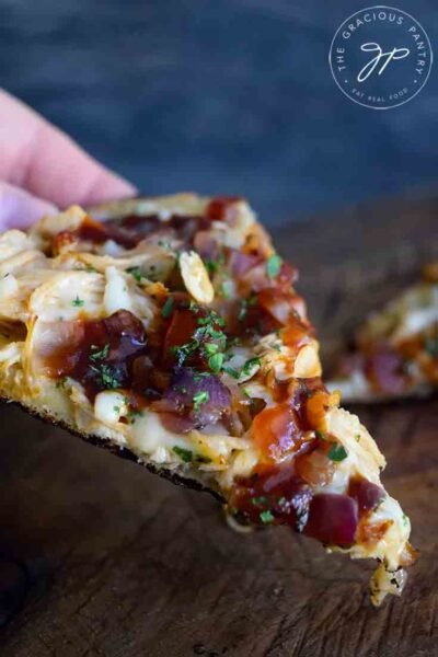 A single slice of this Naan Pizza with barbecue sauce, chicken and caramelized onions.