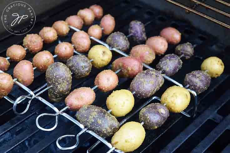 The potatoes on their skewers and skewer rack, roasting on the barbecue.