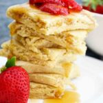 A stack of square, sheet pan pancakes sits piled high with strawberry slices and maple syrup on top.