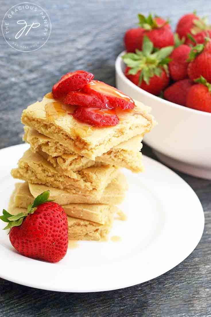 A larger view of a stack of these shee pan pancakes with a large bowl of strawberries sitting behind them.