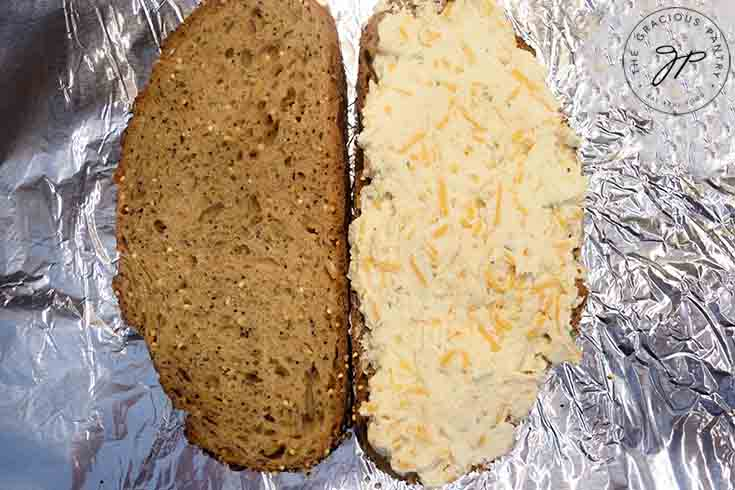 Step four is to spread the cheese over one slice of bread.
