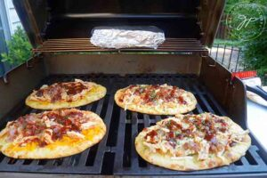 Cook the pizzas on the grill for about 10 minutes.