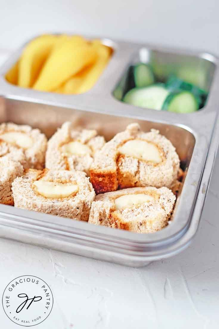 A side view of these Banana Nut Butter Sushi Rolls packed in a bento-style lunchbox.