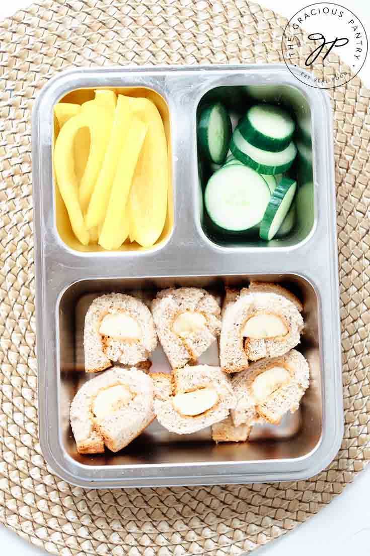 An overhead view of a bento style lunchbox packed with veggies and Banana Nut Butter Sushi Rolls.