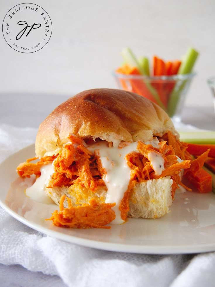 A side shot of these Buffalo Chicken Sandwiches with fresh veggies in the background.