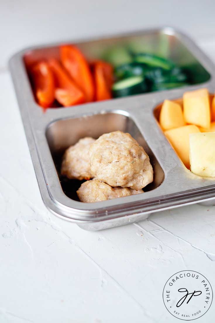 Chicken poppers, along with some cut veggies and fruit fill a bento style lunchbox.