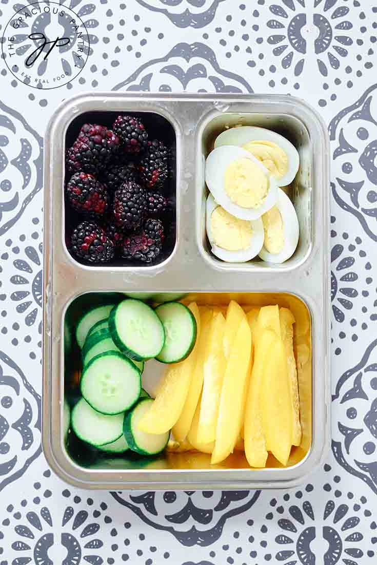 A bento style lunchbox filled with healthy lunchbox snacks.