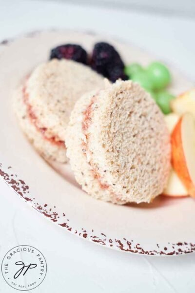 Two Jam Sandwiches on a plate with some cut fruit.