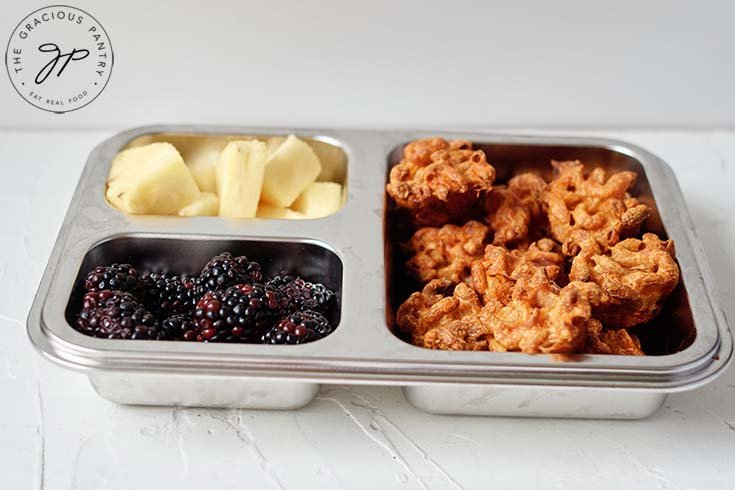 A side view of these mac and cheese bites in a bento box lunchbox.
