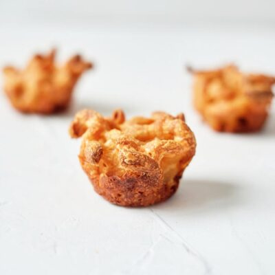 Three mac and cheese bites sit on a white background.