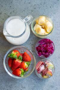 pink dragon fruit smoothie ingredients in individual bowls.