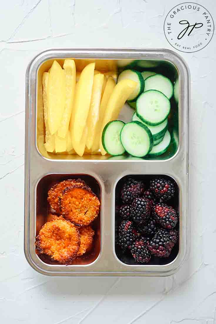 Overhead view of quinoa muffins in a bento-style lunchbox.