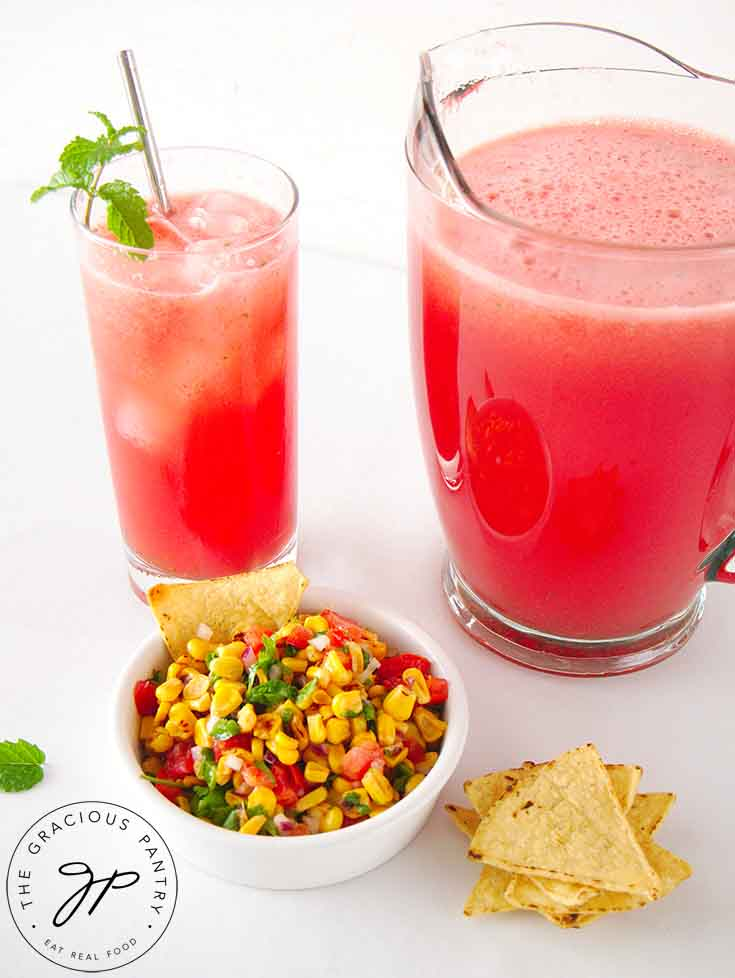 A pitcher and glass both filled, and a bowl of corn salsa with corn chips sitting next to them.