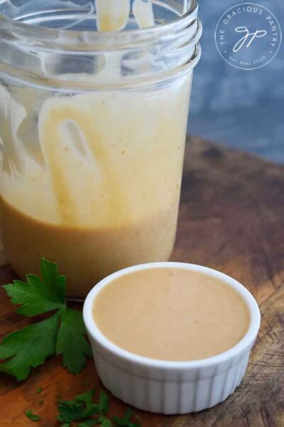 A finished jar of Chick Fil A Sauce sits with a small additional dish of sauce next to it, just served and ready to enjoy.