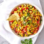 An overhead view of a white bowl filled with this Corn Salsa Recipe.