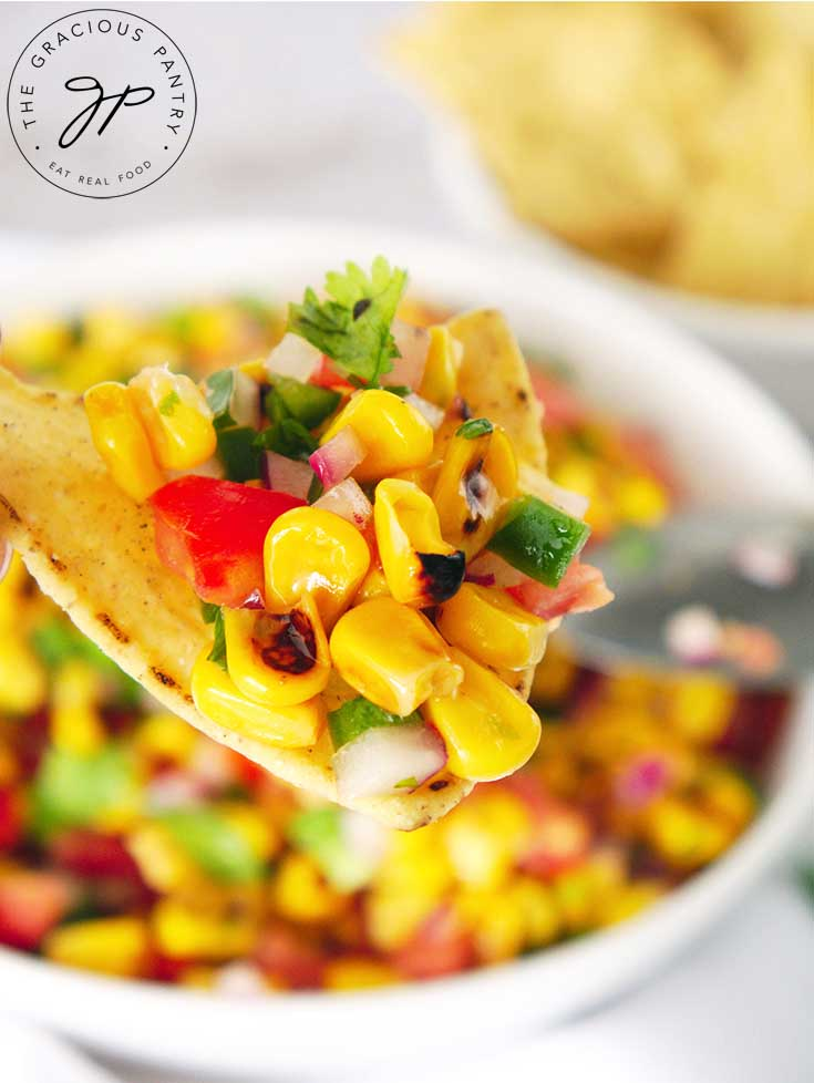 A close up view of a chip holding some of this corn salsa.