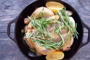 Fresh rosemary sprigs laid over the top of the dutch oven chicken.