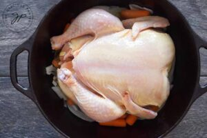 A whole chicken sitting on top of the veggies in the dutch oven.