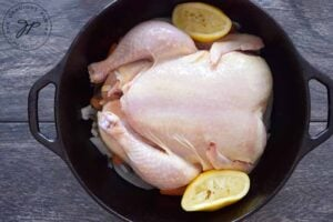 Used lemon halves sit, tucked in on each side of the chicken after the juice has been hand squeezed over the bird.