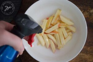 Step 4 - Spritz your apple fries with an oil sprayer and toss.