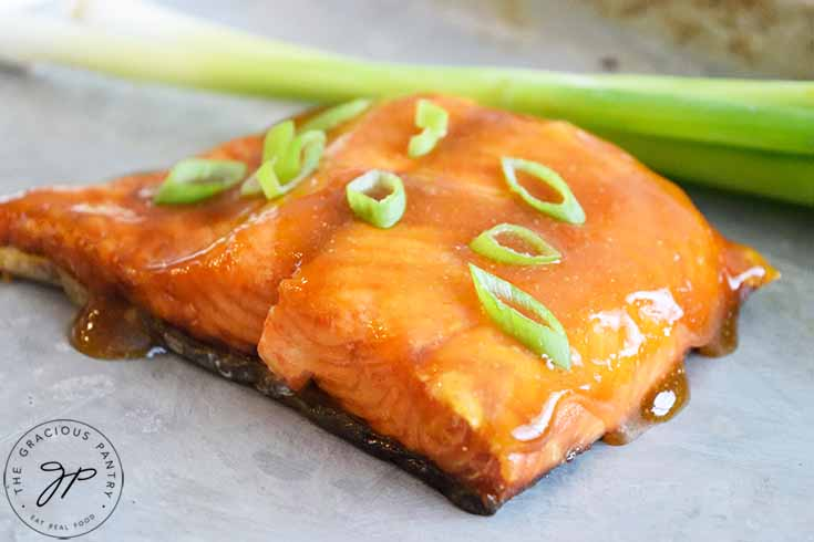 A horizontal shot of a Teriyaki Salmon fillet, just cooked, and glazed with sauce and fresh green onions.