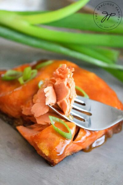 A Teriyaki Salmon Fillet with a fork holding a single bite.