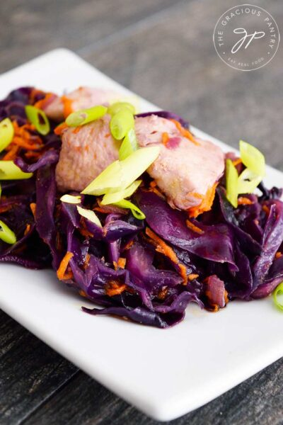 Chicken And Cabbage sits on a white, rectangular plate, ready to serve.