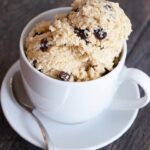 Scoops of this Edible Cookie Dough in a tea cup with a saucer and small spoon.